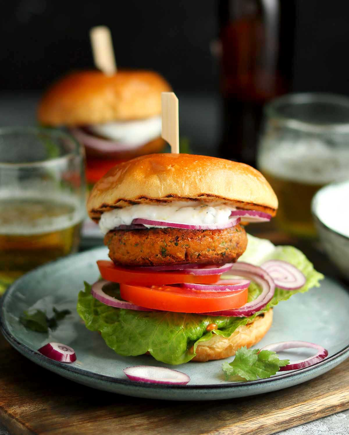 Burgers made with chickpeas and chopped red onion, served in a bun with lettuce, tomato and minty yoghurt sauce.