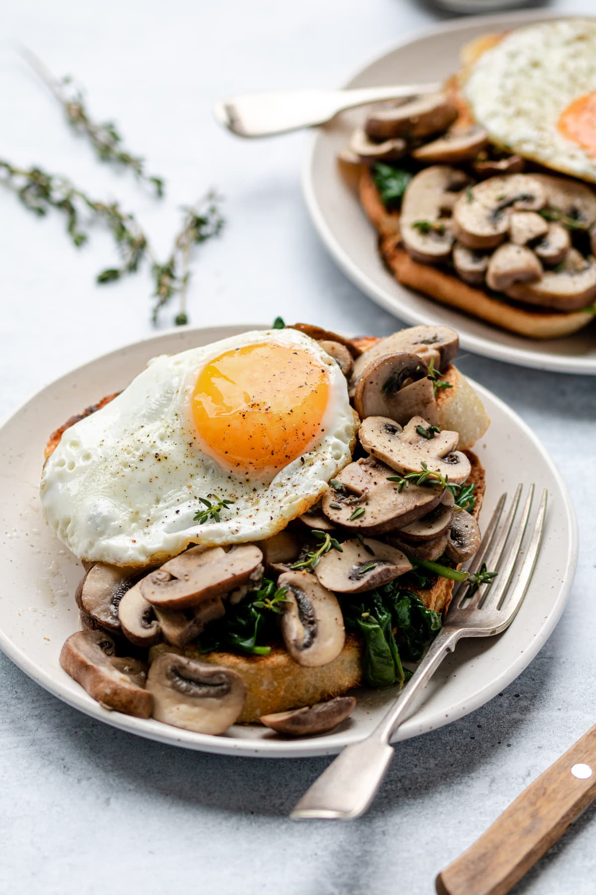 Mushrooms and wilted spinach on toasted sourdough bread topped with an egg