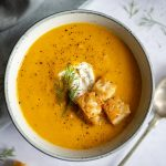 Carrot soup in bowls with croutons and yoghurt.