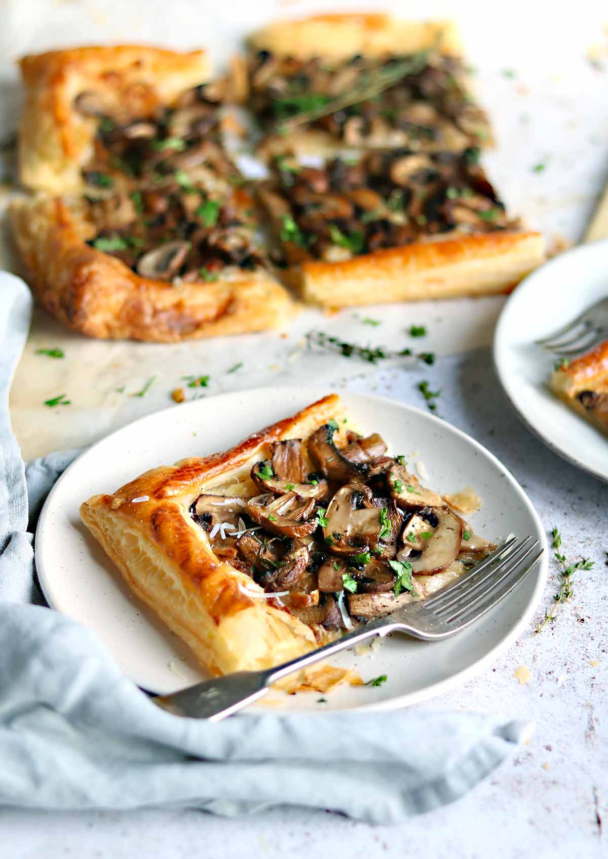 Chestnut mushrooms on a puff pastry bed, with parsley and thyme and shavings of italian hard cheese.