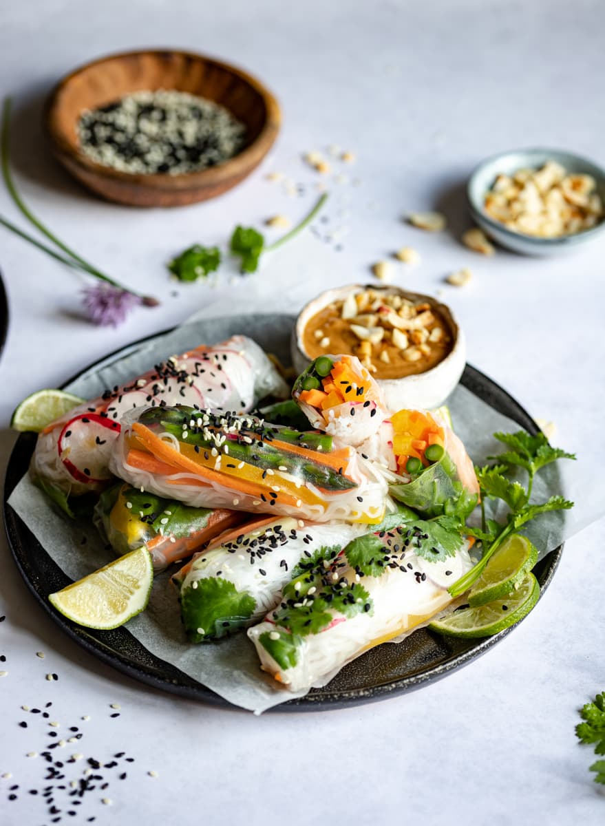 Paper rolls packed with vegetables, a peanut dipping sauce, limes and coriander