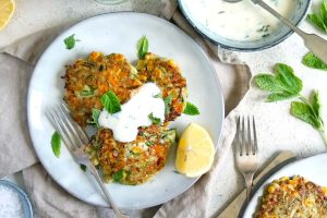 Courgette and Sweetcorn Fritters with mint in yoghurt sauce and lemon wedges.