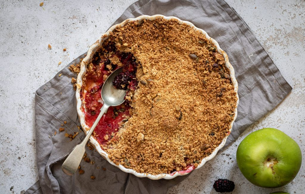 Landscape image of apple and blackberry crumble in a pie dish with a spoon