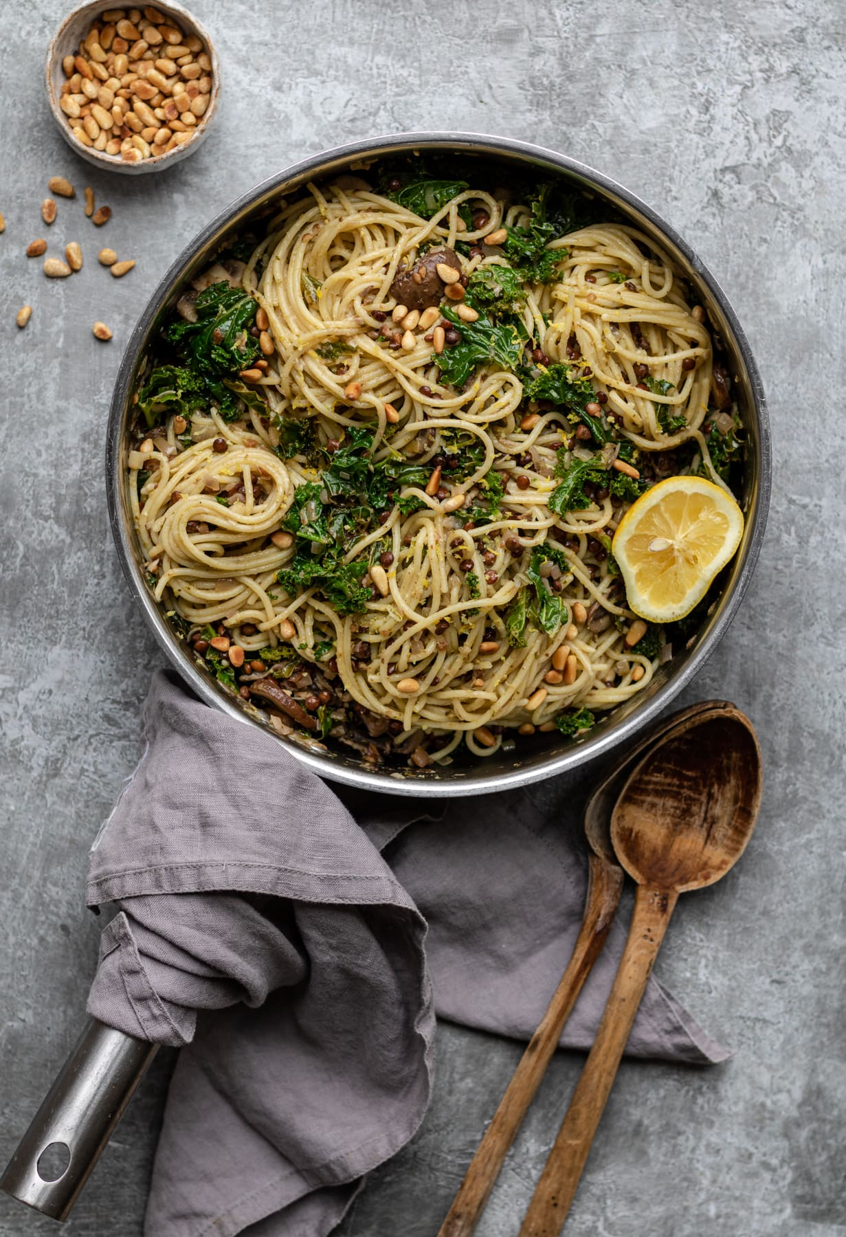 spaghetti with mushrooms in pan sprinkled with pine nuts