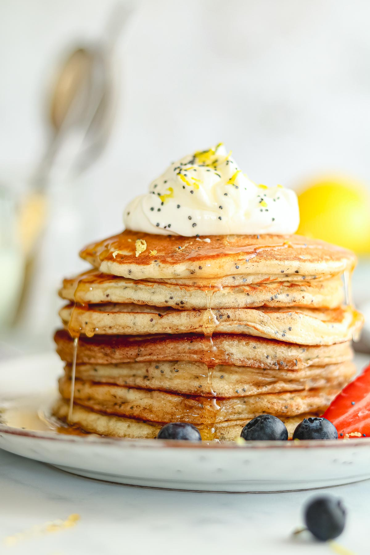 Lemon Buttermilk Pancakes with poppy seeds, yoghurt and strawberries, with maple syrup pour.