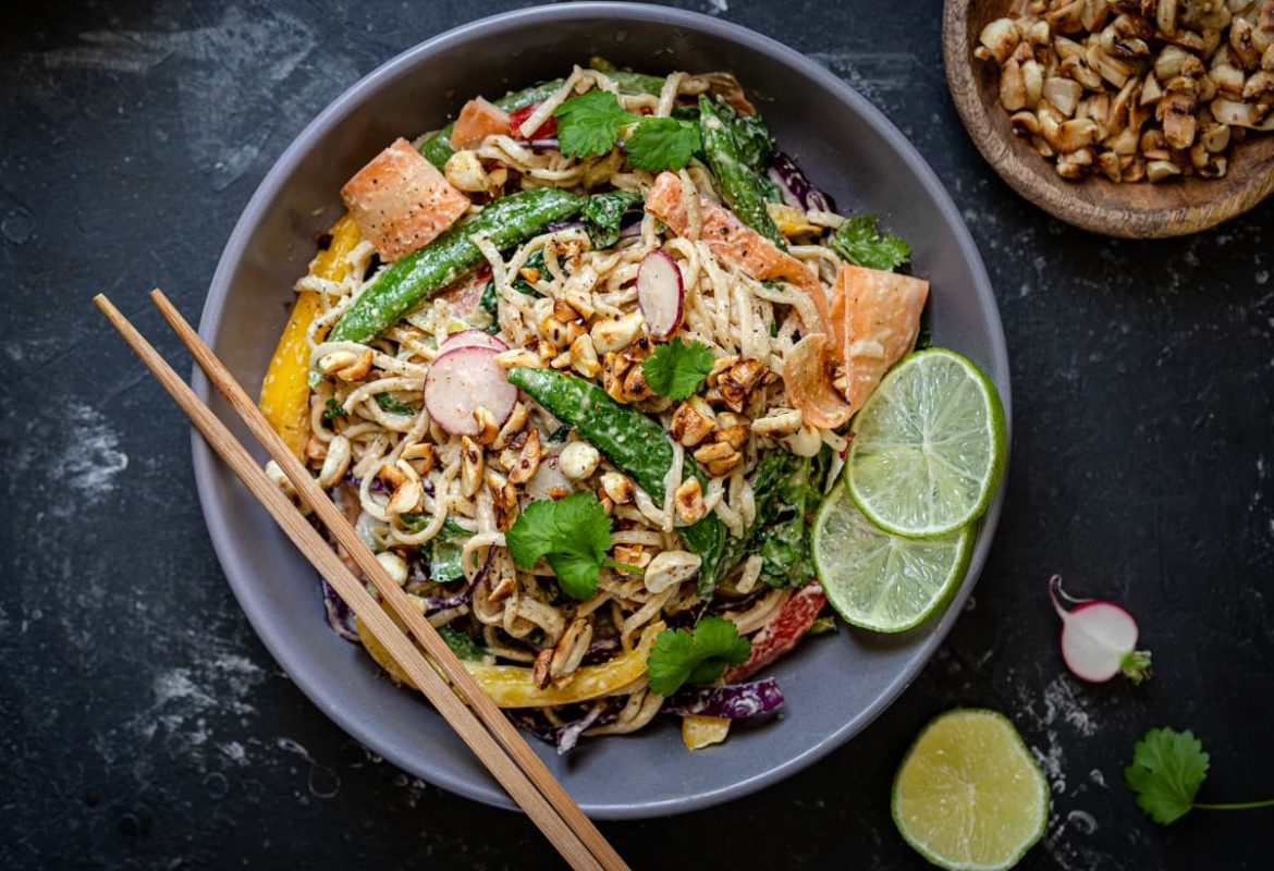 Noodles with spinach, carrots, peppers, mange tout and spring onions in a peanut dressing