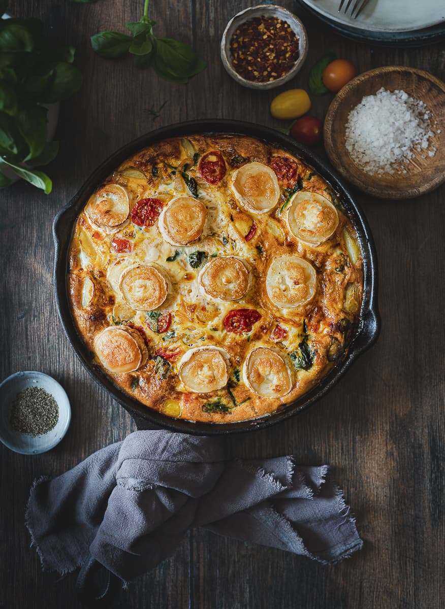 Frittata with Spinach, cheese, potatoes and Tomatoes in a skillet