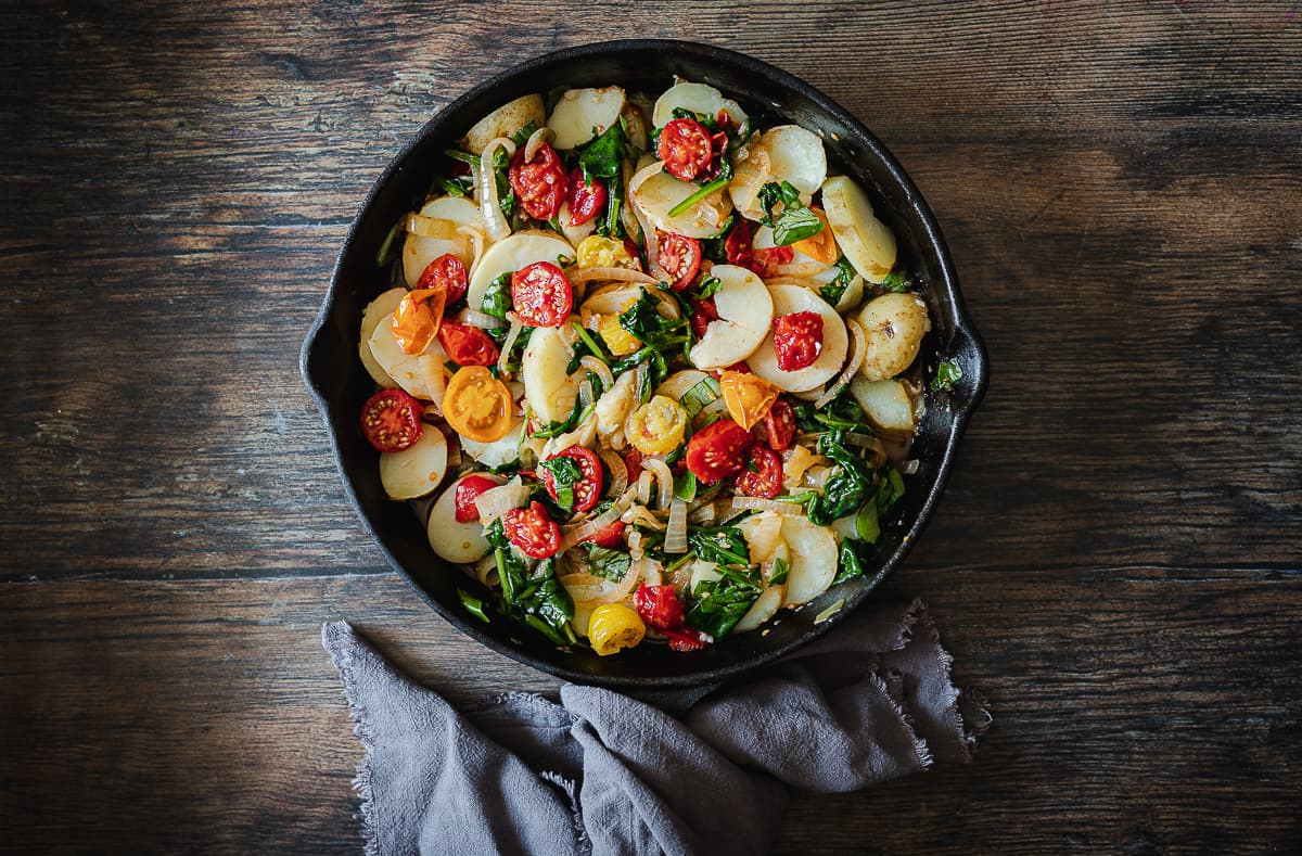 tomatoes, onions, potatoes and spinach cooking in skillet