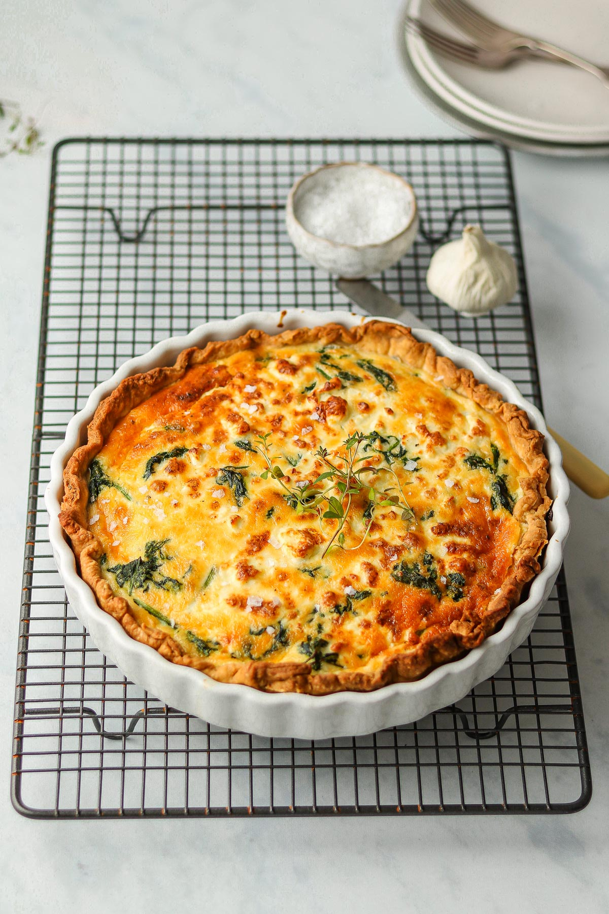spinach and feta quiche in pie dish on a cooling rack
