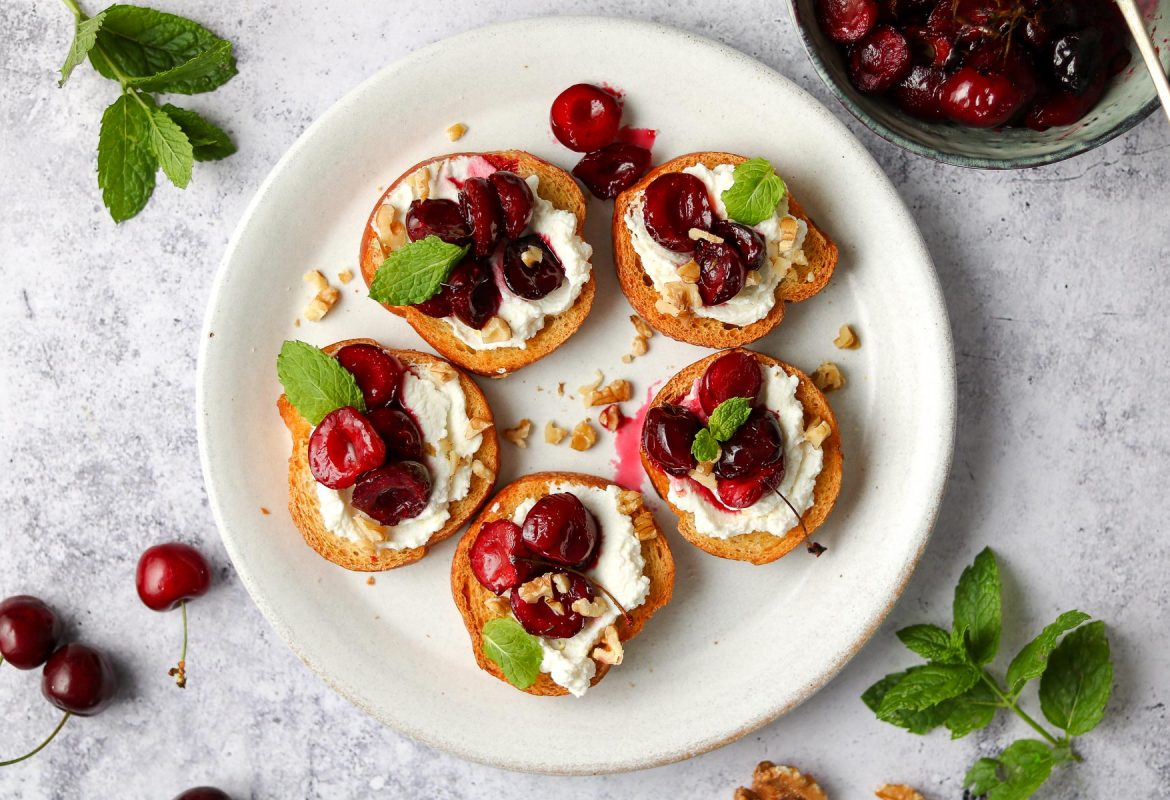 Ricotta crostini with roasted cherries on a serving plate.
