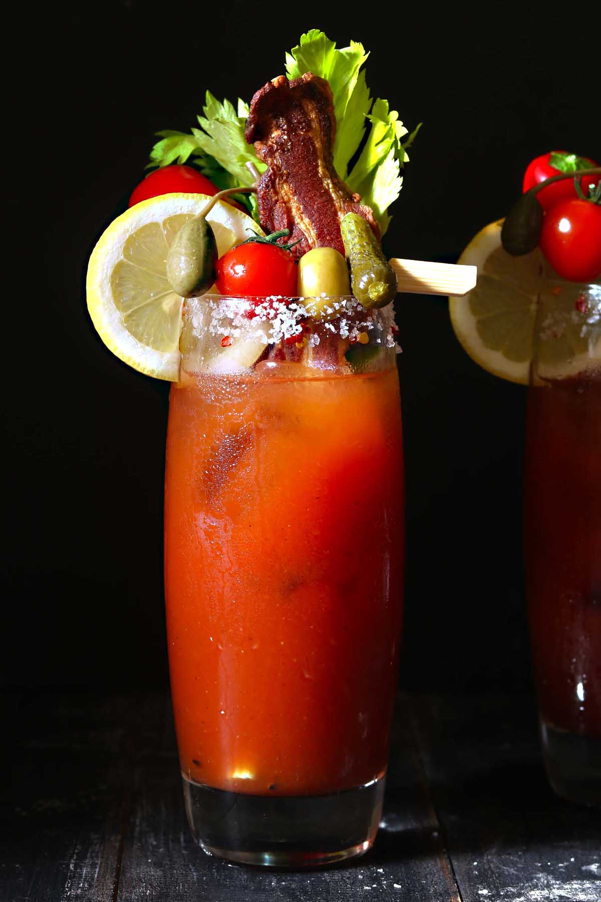 Bloody mary drink with lemon, celery, olives, cornichons and caper berries.
