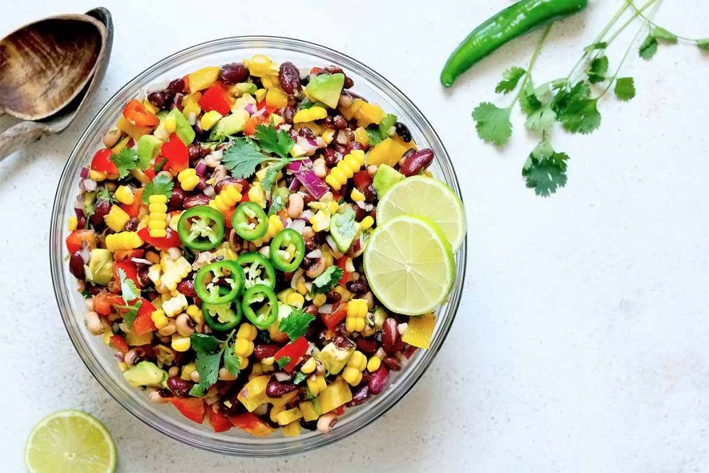 A salad made with beans, onion, peppers, avocado, slices of jalapeño, lime wedges