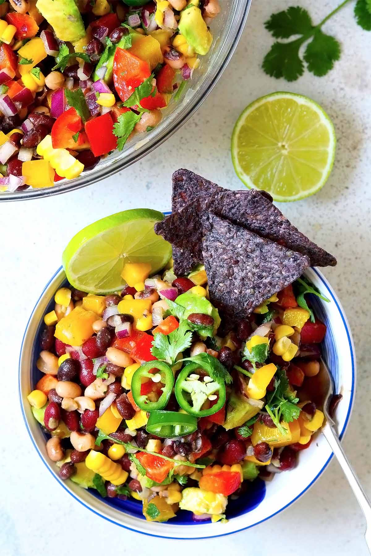 A salad made with beans, onion, peppers, avocado, slices of jalapeño, lime wedges and corn tortillas