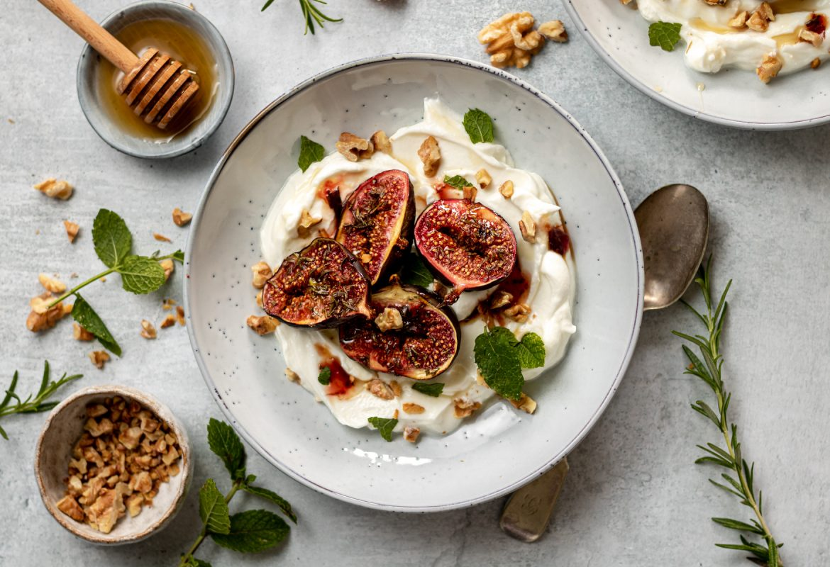 overhead photo of roasted figs in a bowl with yoghurt and chopped nuts.