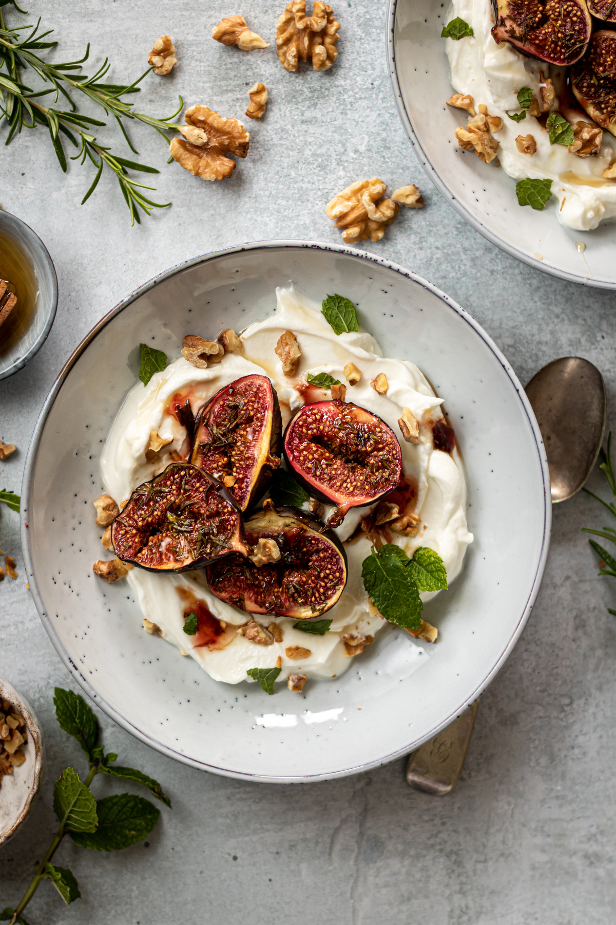 Roasted figs on a bed of yoghurt, topped with chopped walnuts and mint leaves
