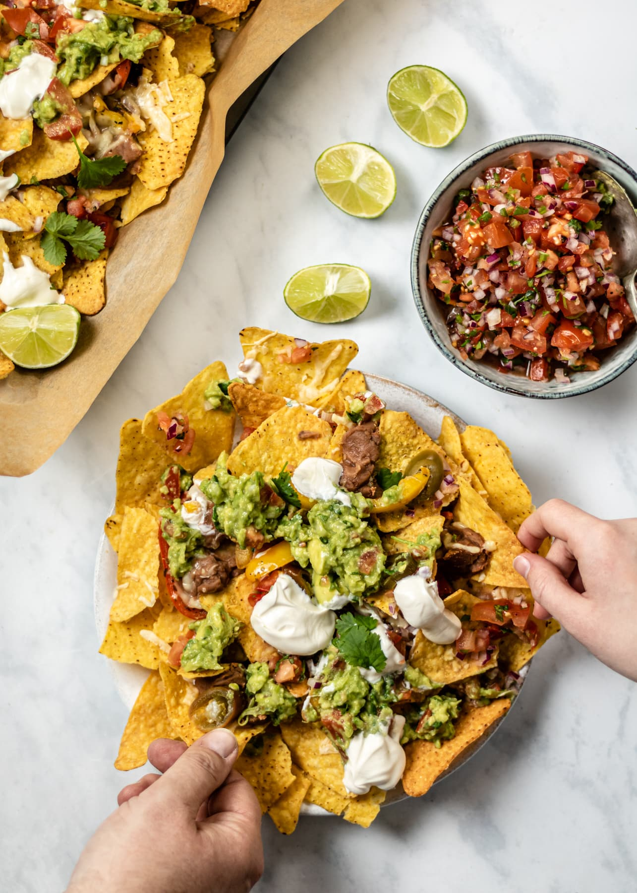 Loaded veggie nachos on a plate with two people taking some nachos from the plate