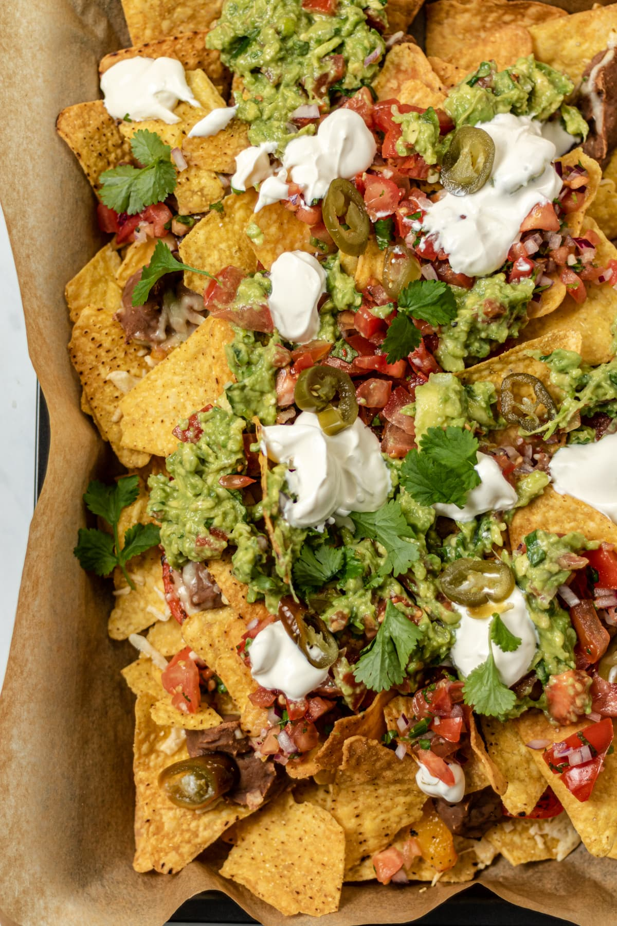 Close up mage of veggie nachos with salsa, guacamole and sour cream on top