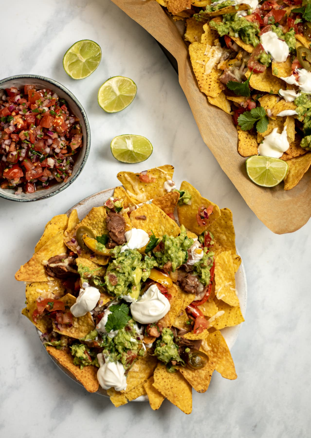 Nachos on a plate with lime wedges and a bowl of salsa beside them