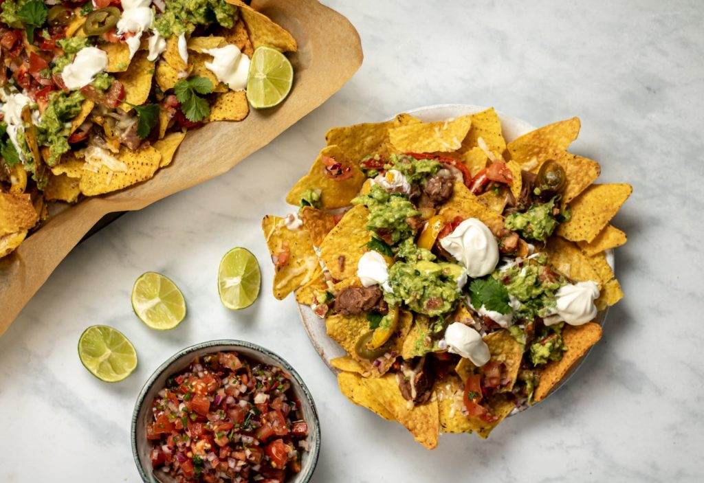 landscape image of nachos on a plate with a bowl of salsa on the side and lime wedges nearby