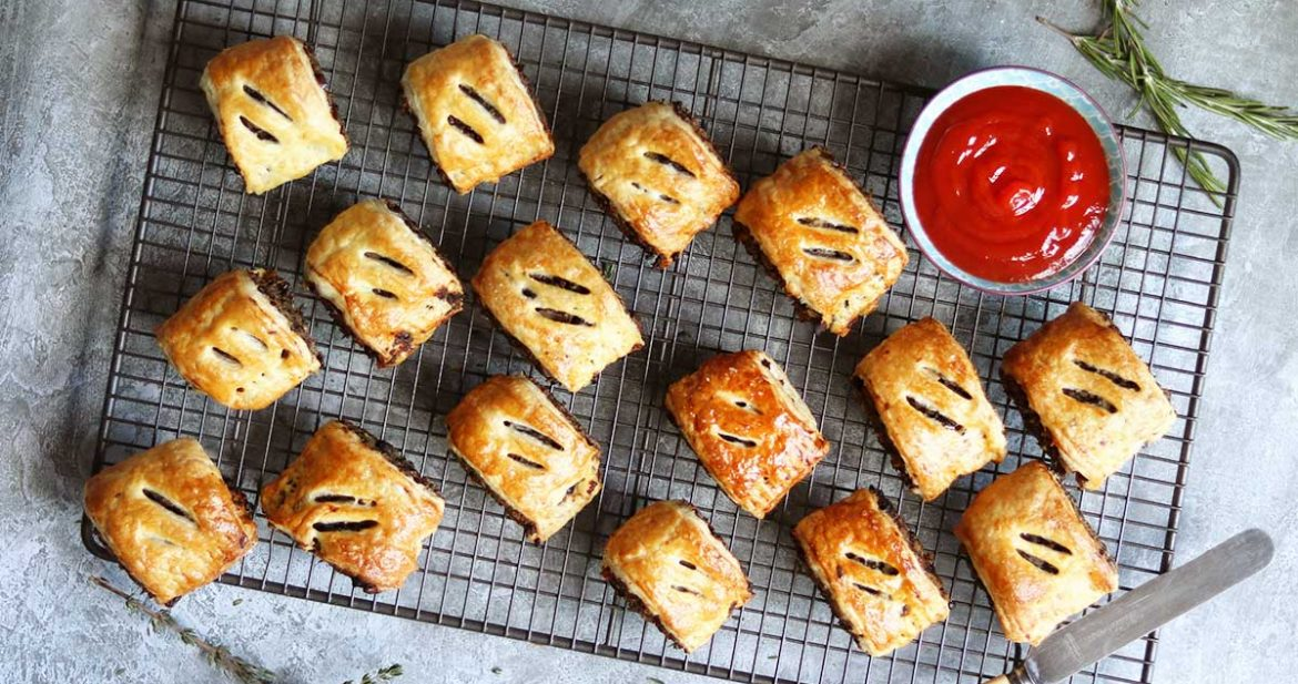 sausage rolls on baking tray with ketchup