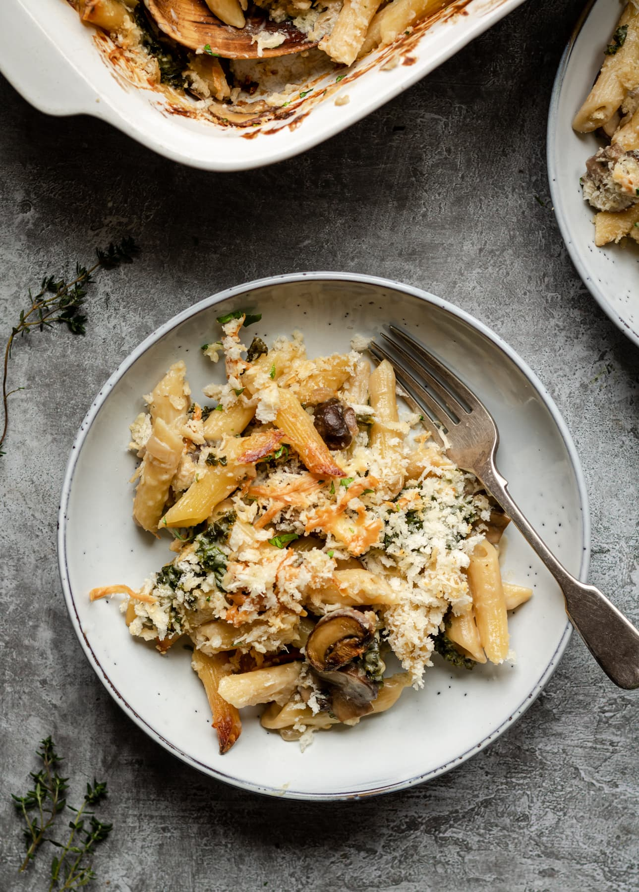 Pasta in a creamy sauce, with mushrooms and kale covered in breadcrumbs