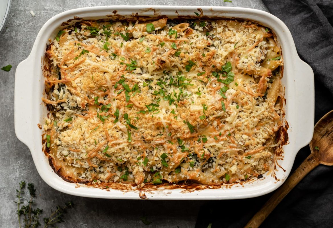 Pasta in a creamy sauce, with mushrooms and kale covered in breadcrumbs in a dish
