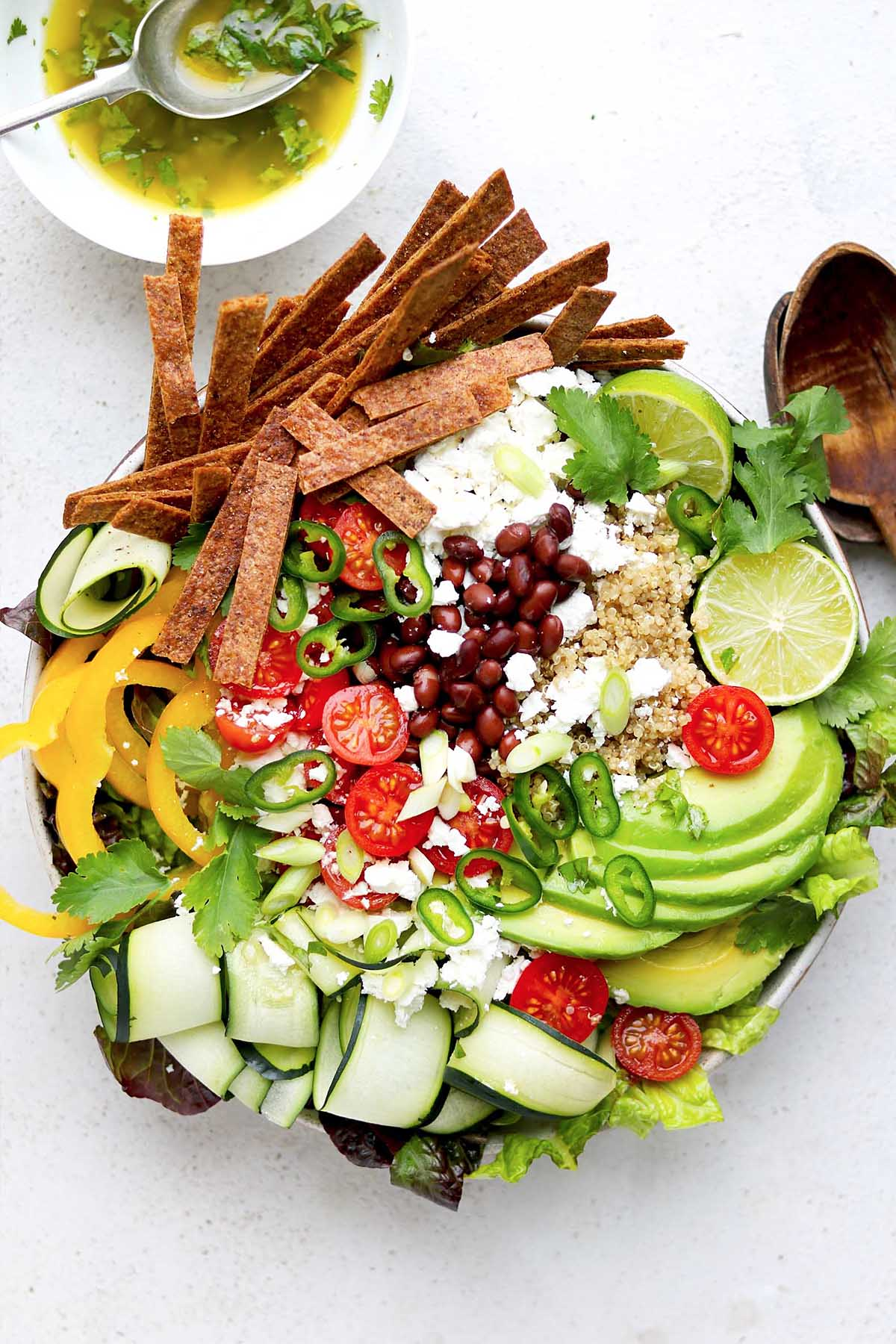 Taco salad bowl full of avocado , tomatoes, lime, taco stripes and peppers, feta and herbs