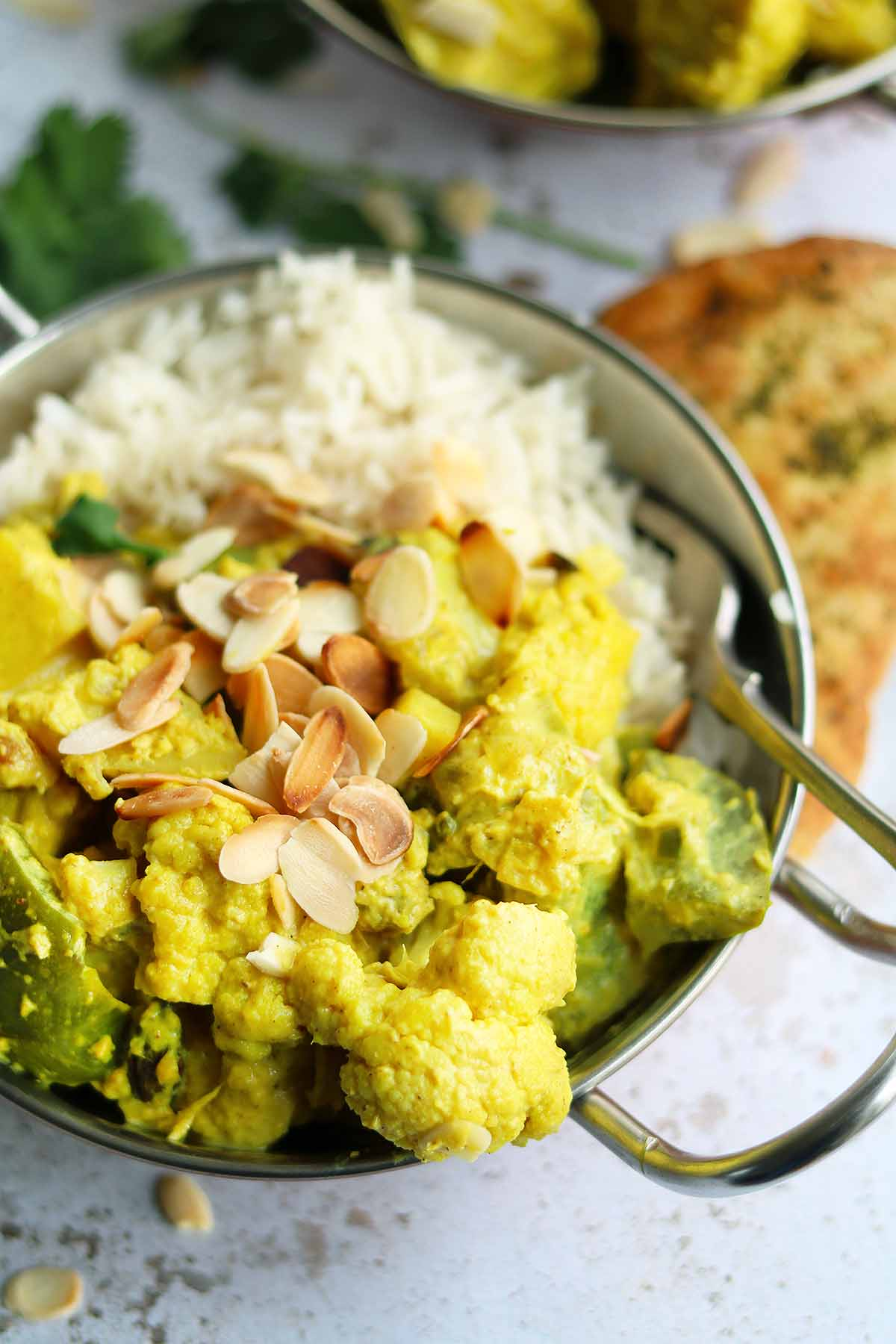 Cauliflower with green peppers, potatoes and sultanas covered in a korma sauce with coriander and almonds, served with rice.