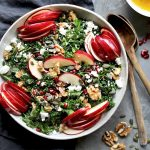 Sliced red gala apples with kale, feta, walnut halves, pumpkin seeds and pomegranate served in a bowl.