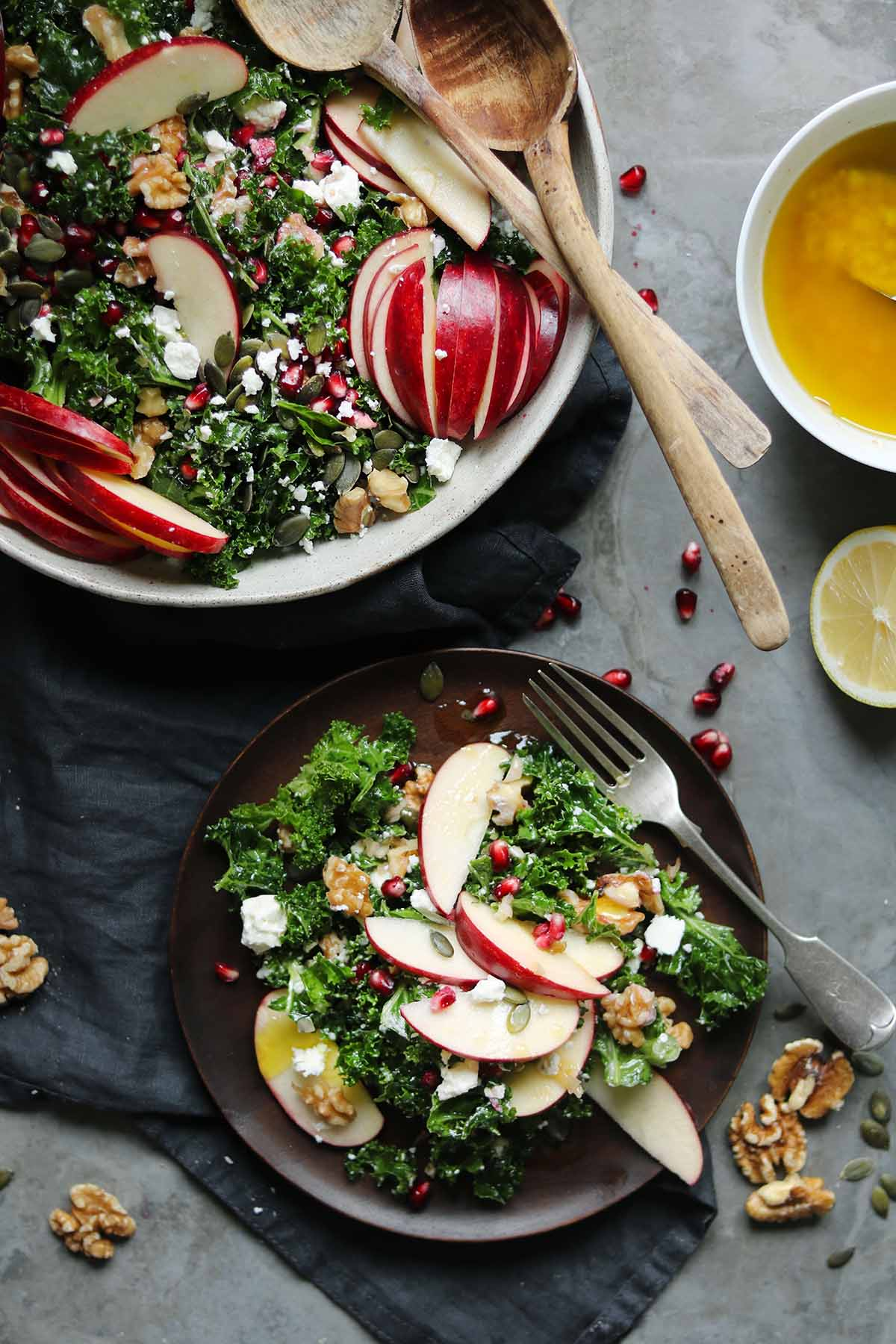 Sliced red gala apples with kale, feta, walnut halves, pumpkin seeds and pomegranate served on a plate.