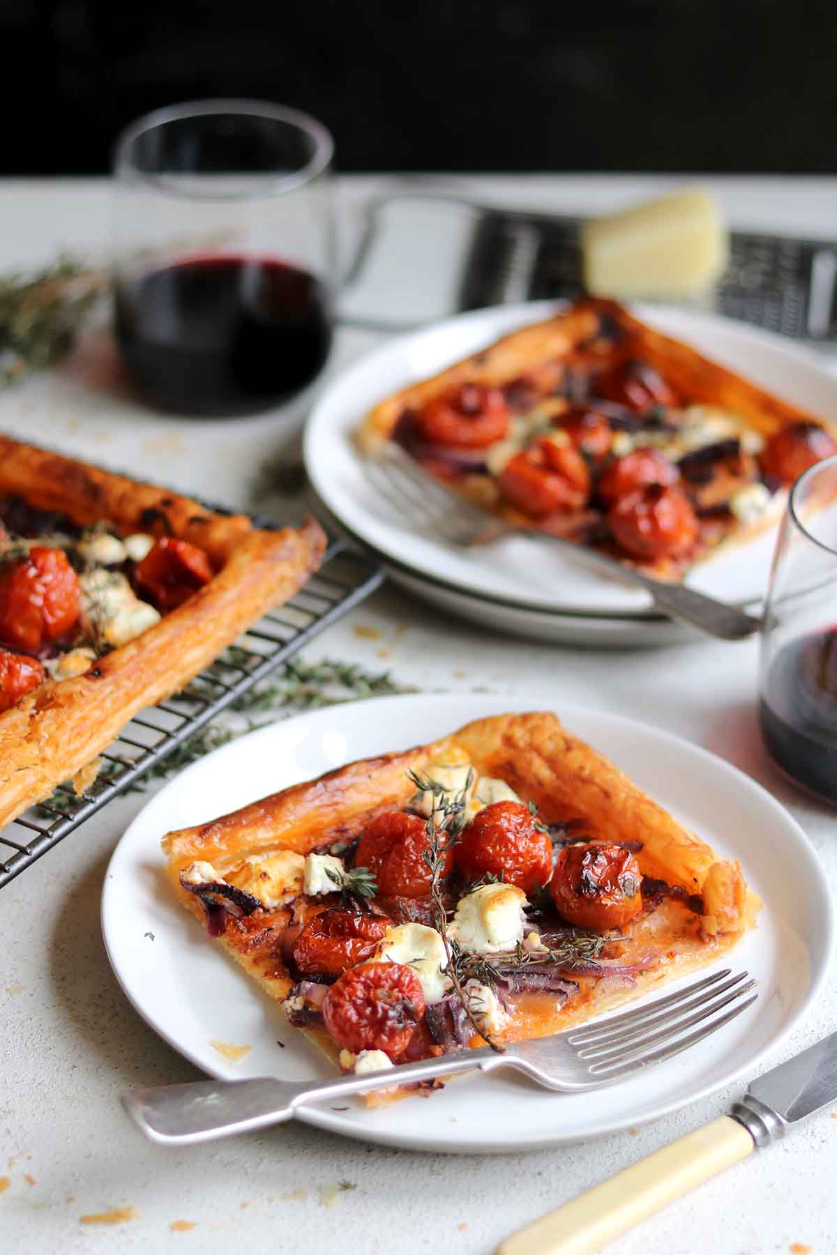 A pastry tart with balsamic roasted tomatoes, goats cheese, with red onions and herbs