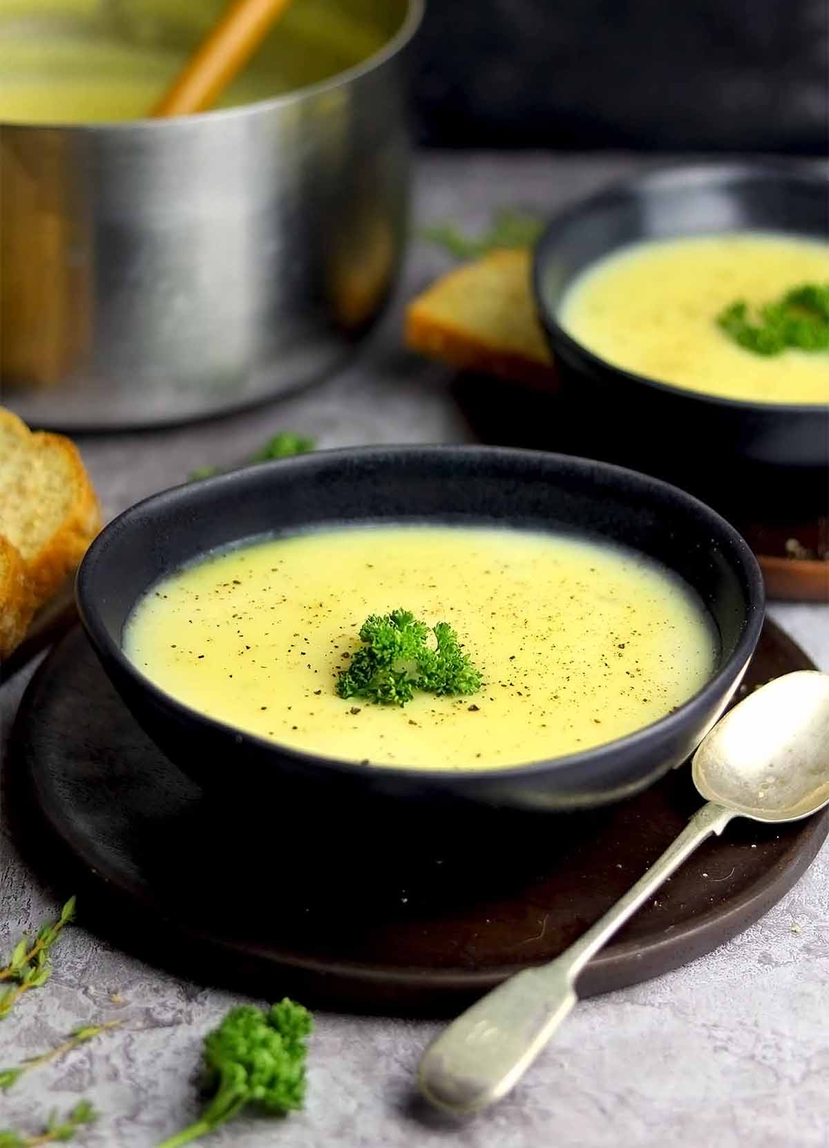 Potato Soup with parsley and bread in bowls