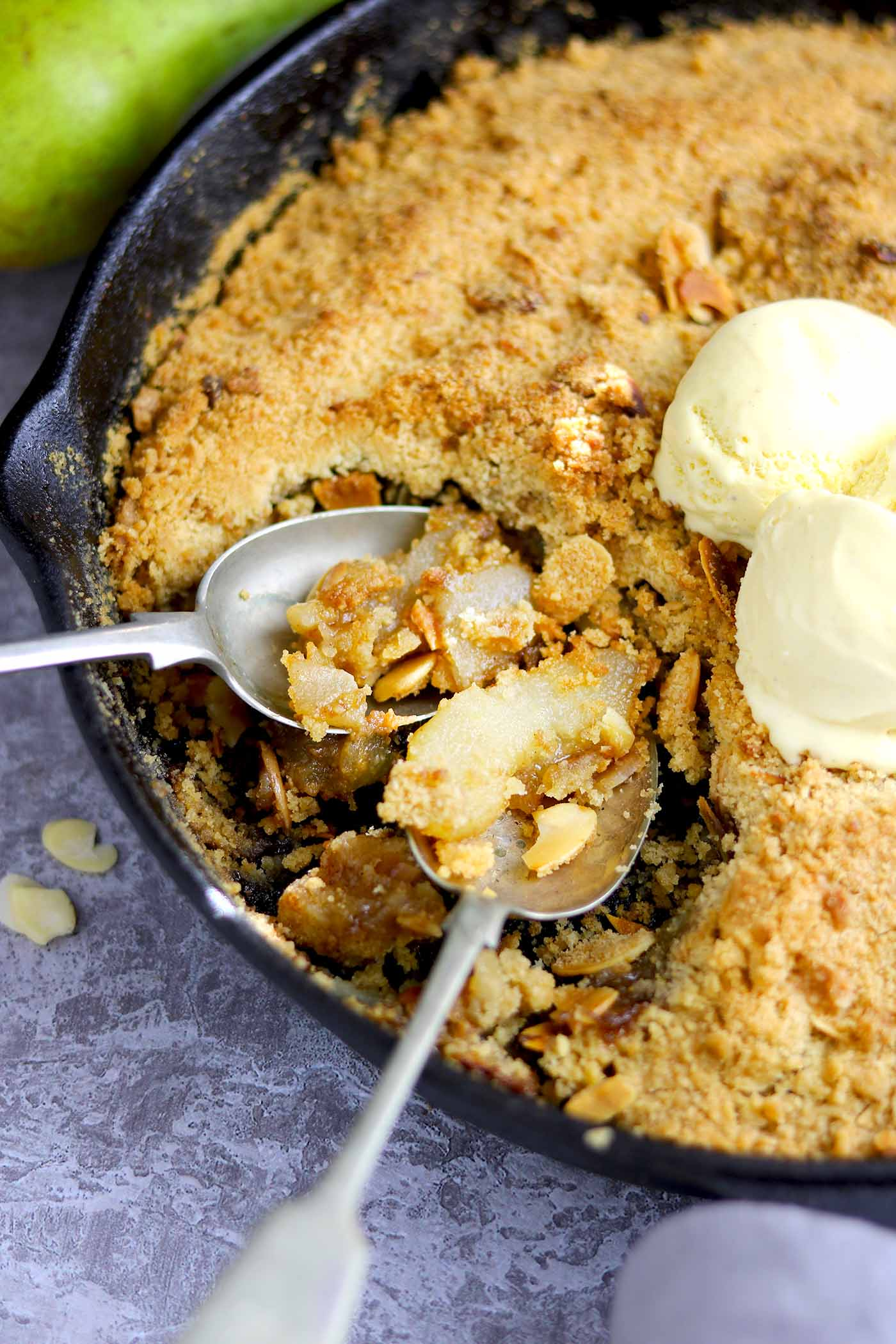 pear crumble in skillet with spoons