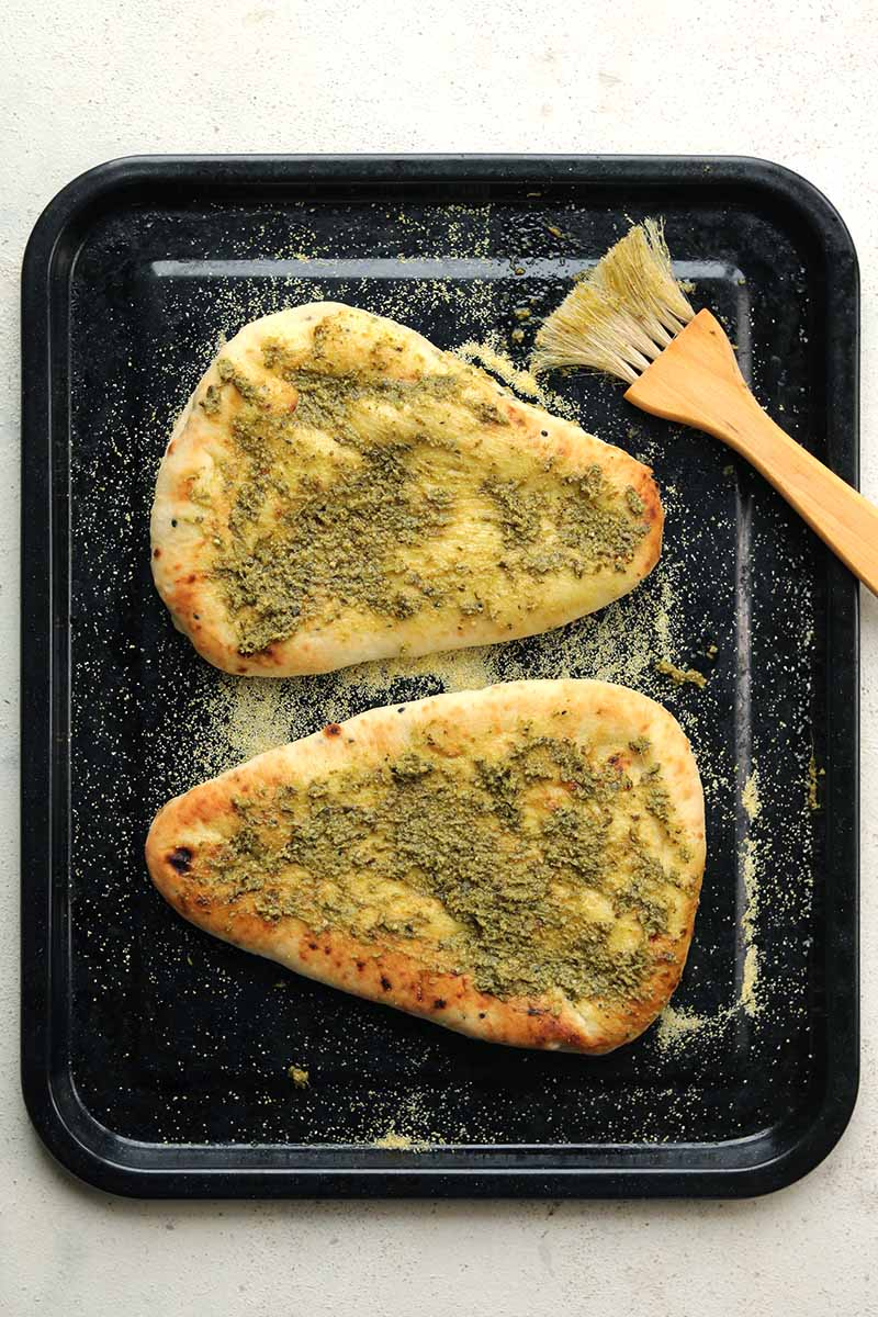 pesto on pizza base in baking tin
