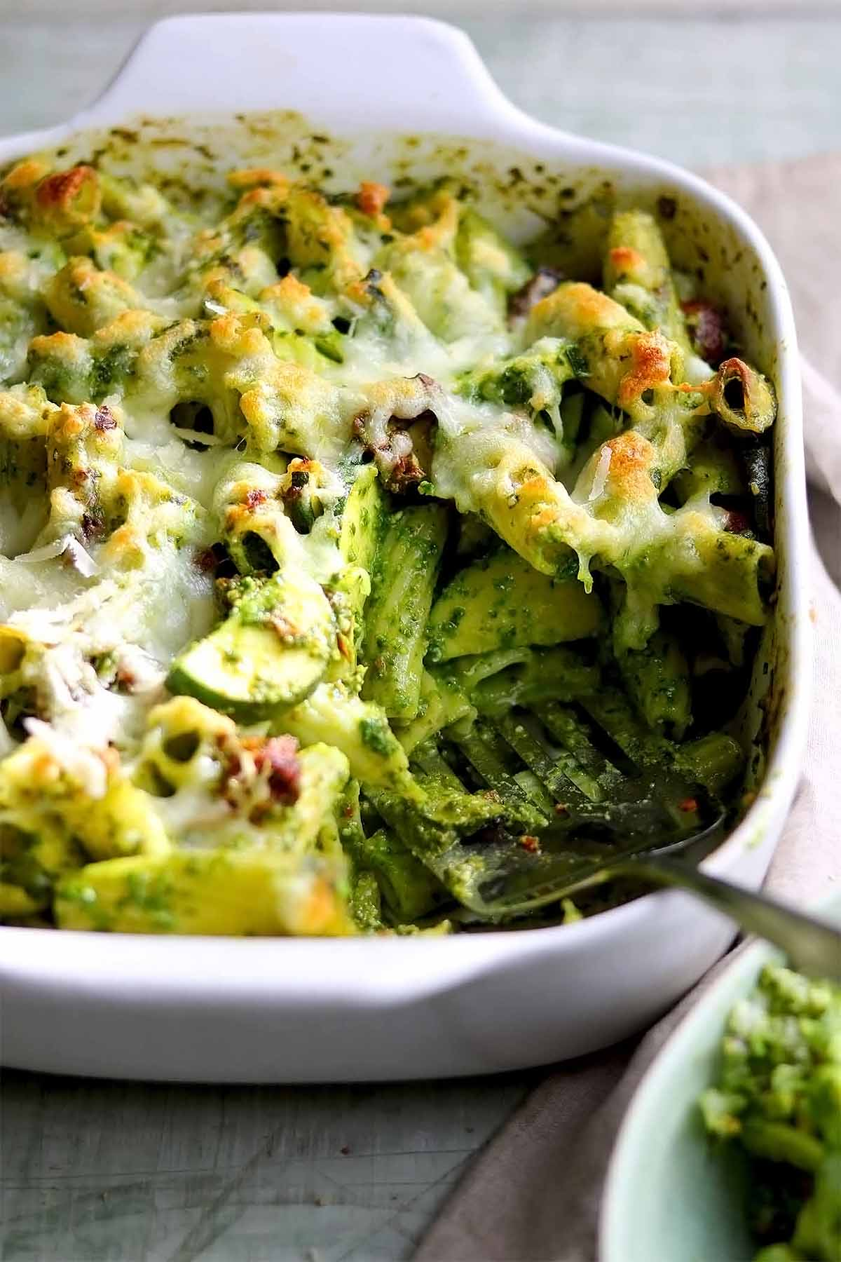 Pasta in pesto with courgettes & sun-dried tomatoes and melted cheese