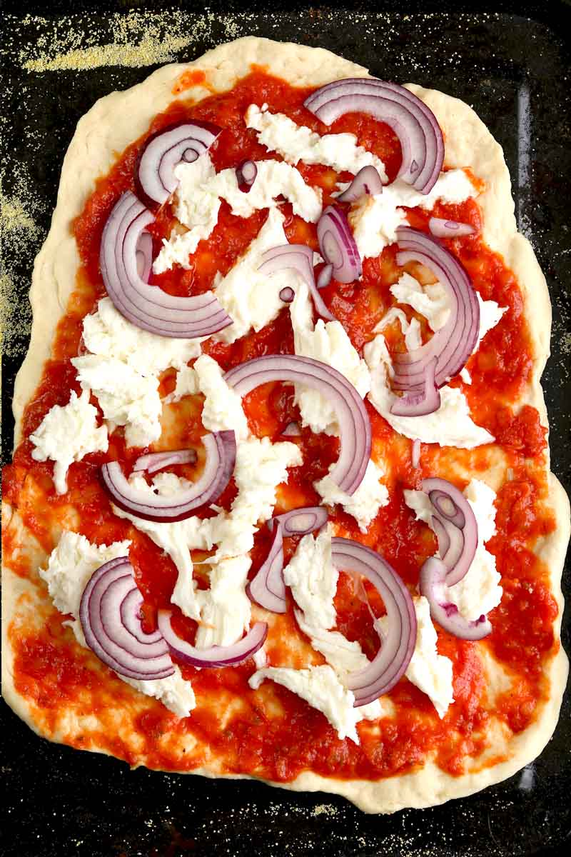 uncooked pizza base with toppings