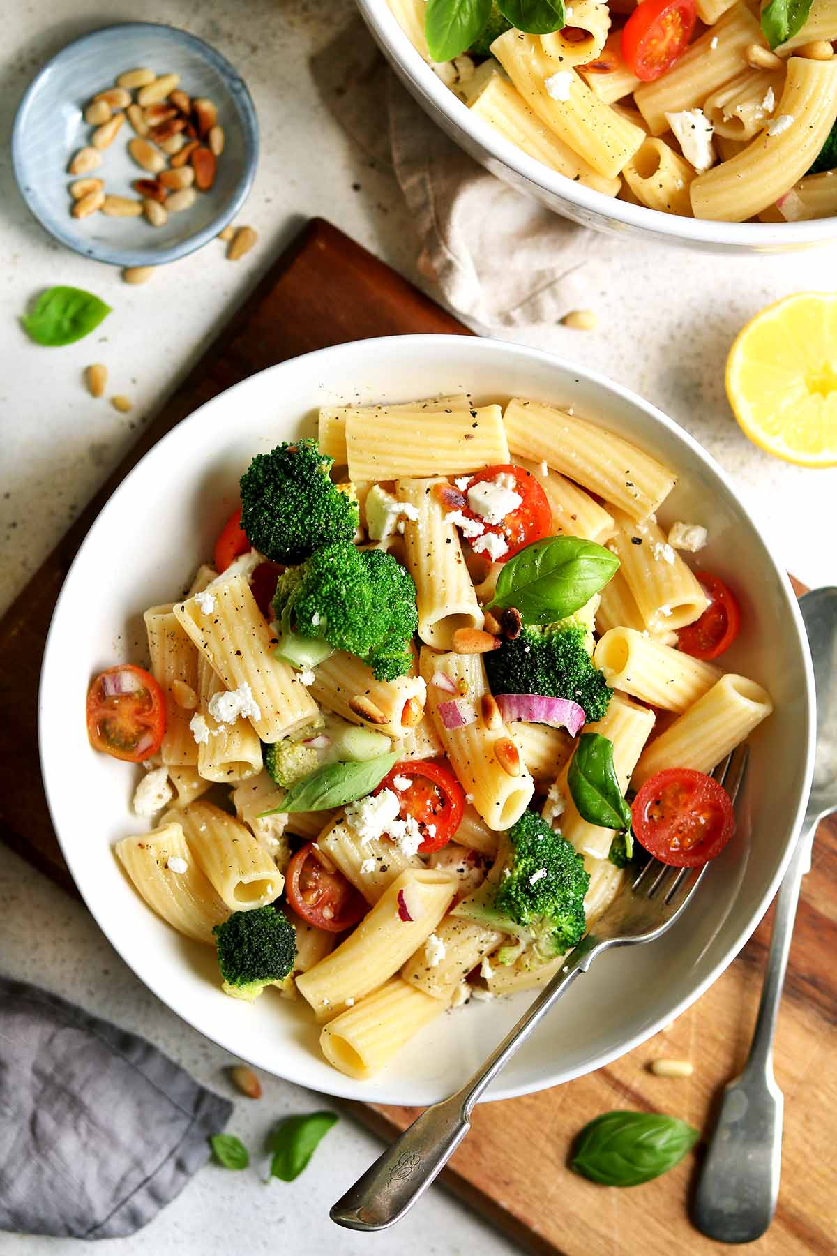 A pasta salad made with broccoli, tomatoes, feta, basil and pine nuts on a chopping board