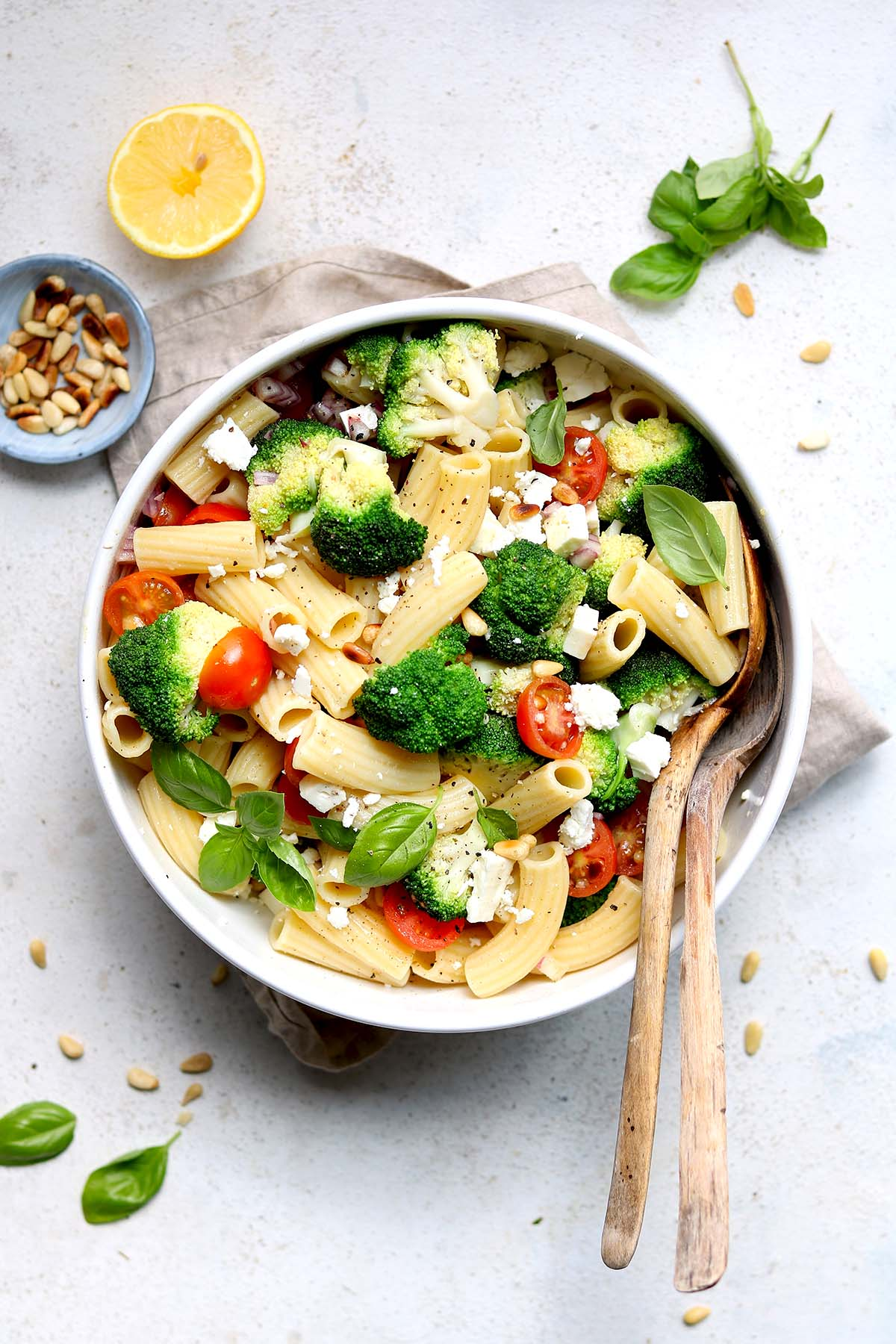 A pasta salad made with broccoli, tomatoes, feta, basil and pine nuts