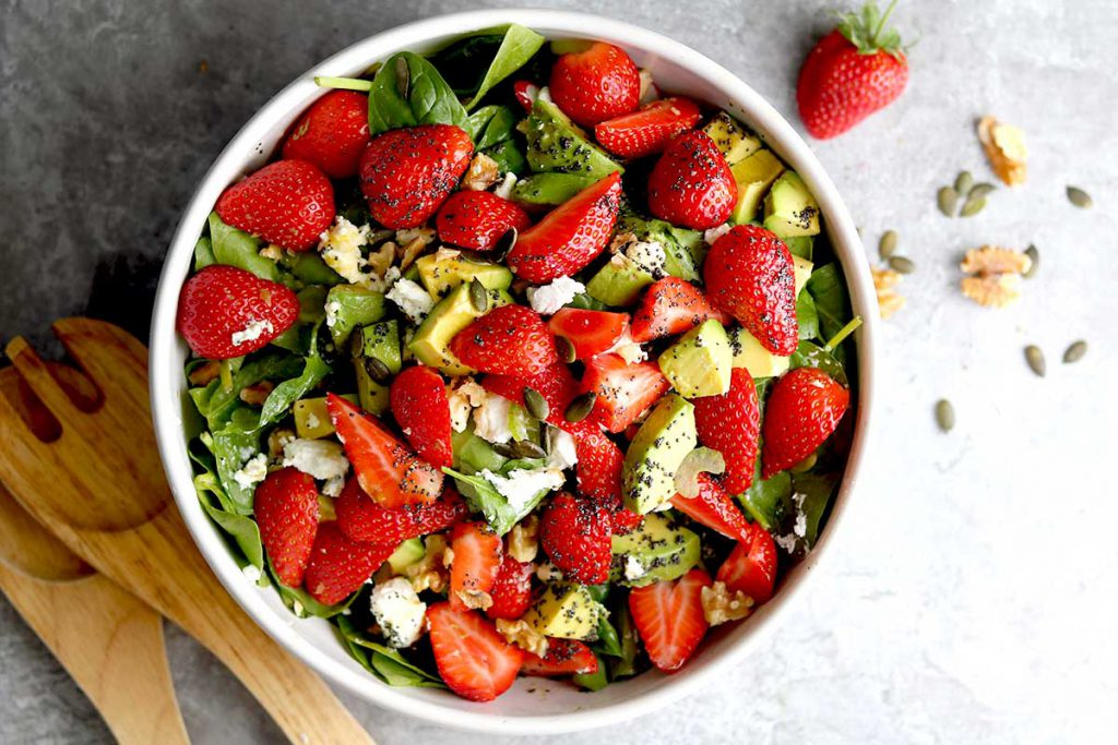 A bowl full of spinach, strawberry's, walnut and avocado in a poppy seed dressing