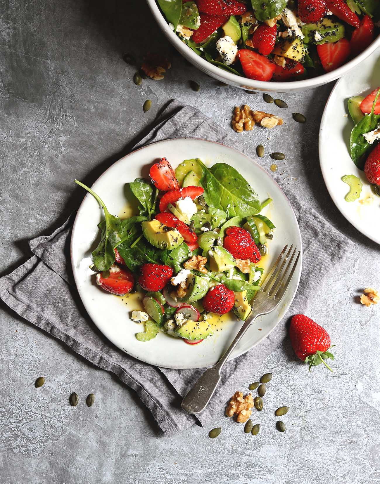 A plate of spinach, strawberry's, walnut and avocado in a poppy seed dressing
