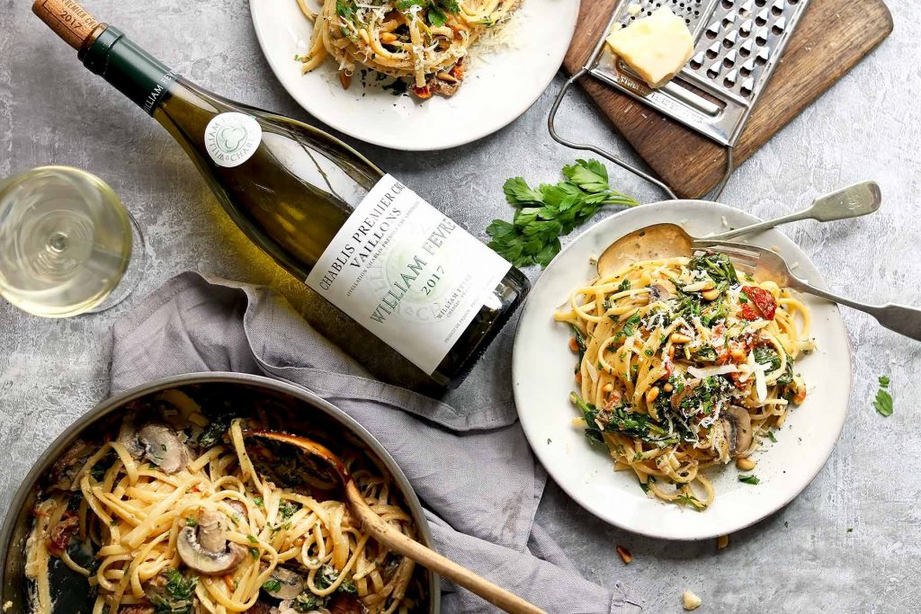Pasta with Mushrooms, Spinach, sun-dried tomatoes in white wine sauce with a wine glass and bottle of wine