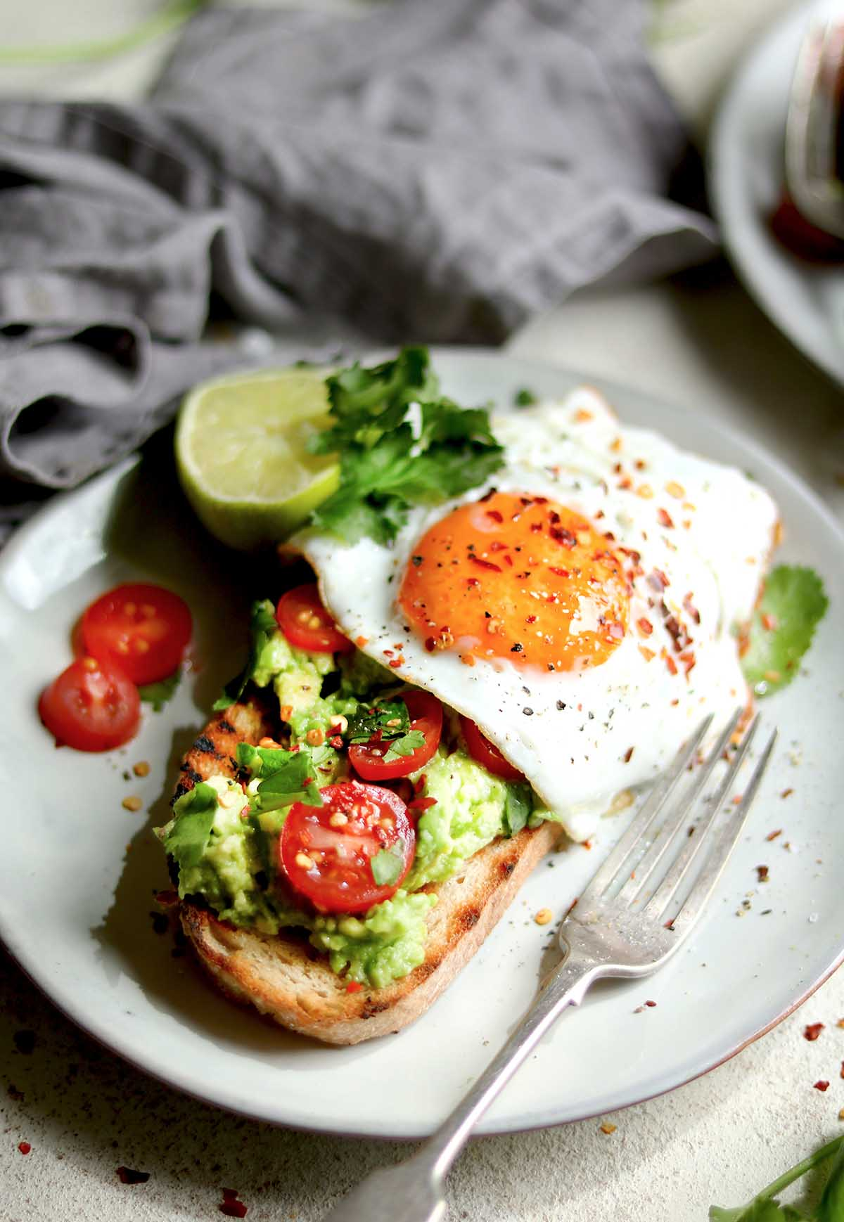 Avocado, Toast with a fried egg, tomatoes, lime and coriander