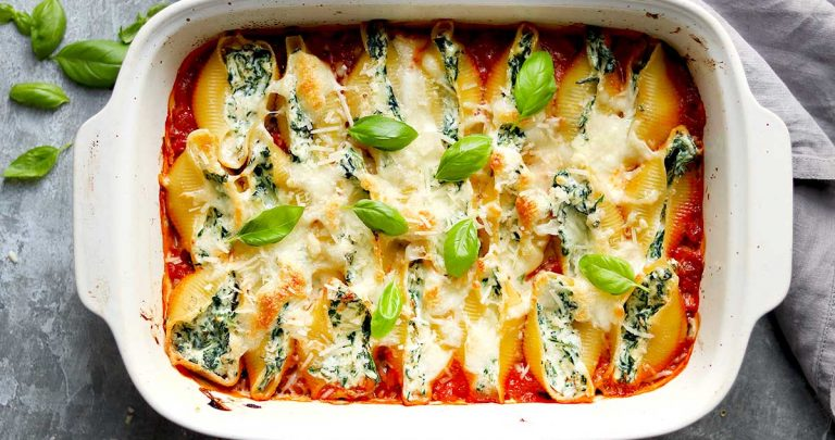 Pasta Shells filled with Spinach and Ricotta in tomato sauce with basil leaves in a dish.