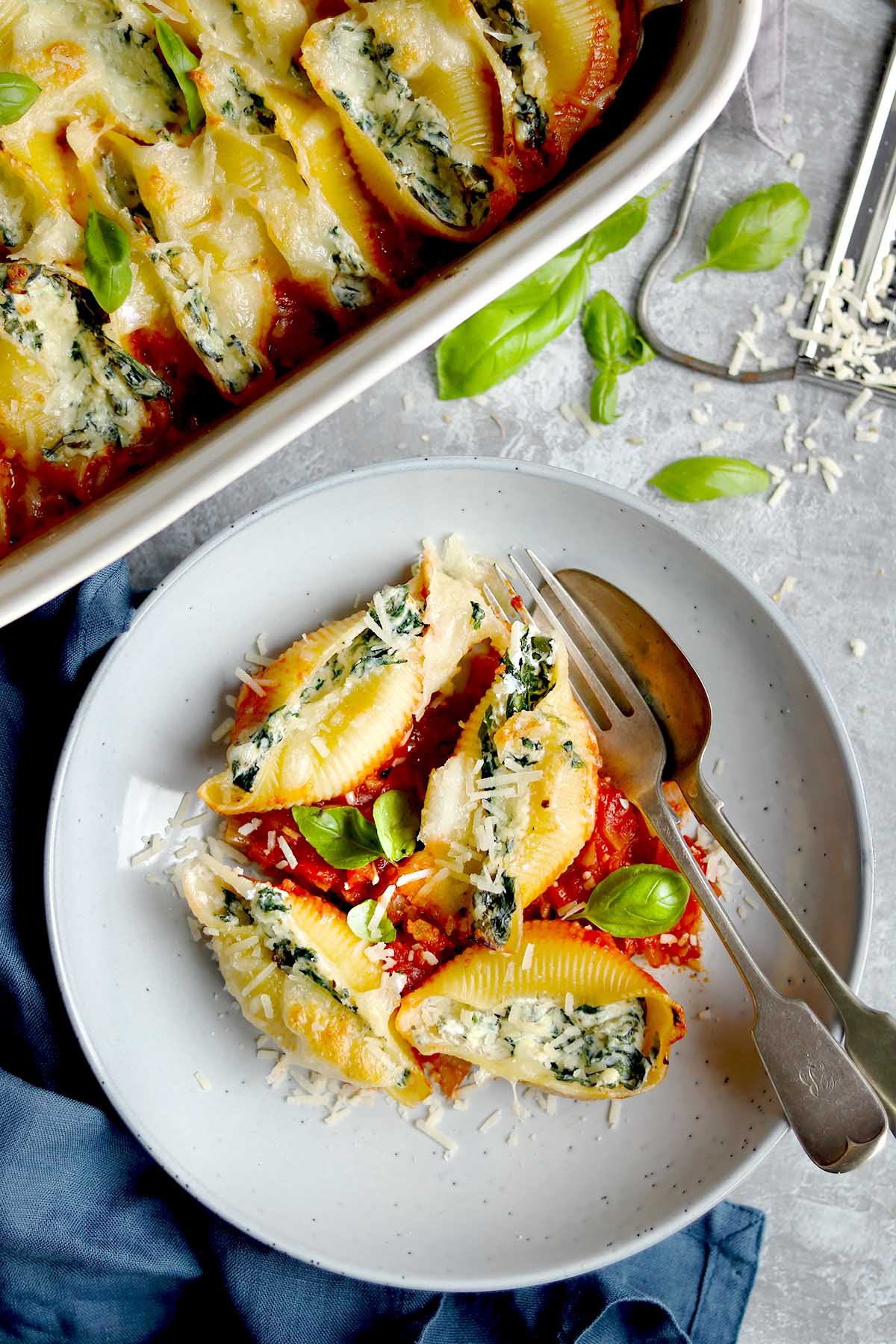Pasta Shells filled with Spinach and Ricotta in tomato sauce with basil leaves served on a plate.