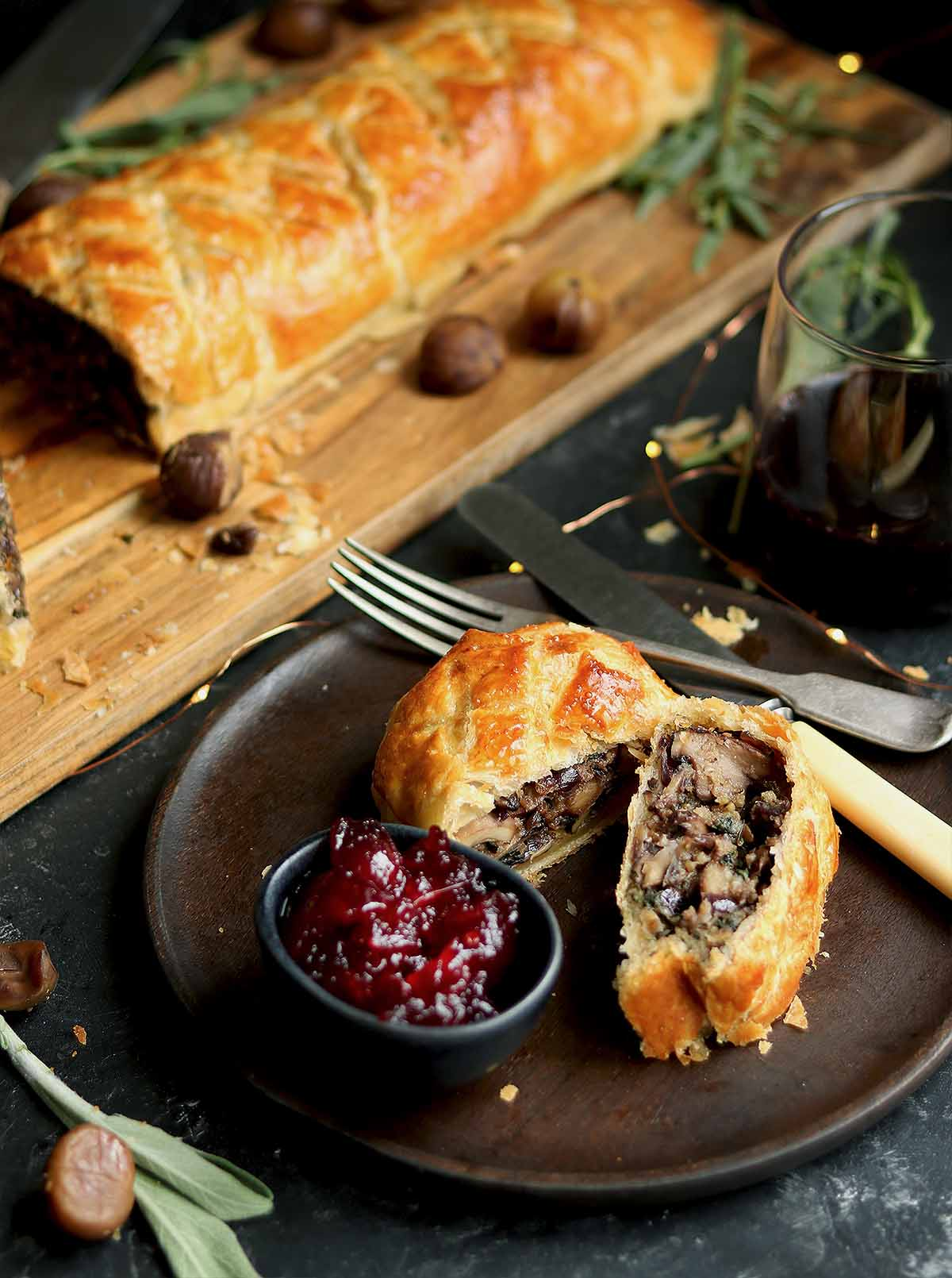 A mushroom mixture with chestnuts, spinach, caramelised onions, wrapped in puff pastry as a wellington, with a cranberry sauce, sage, and tarragon.