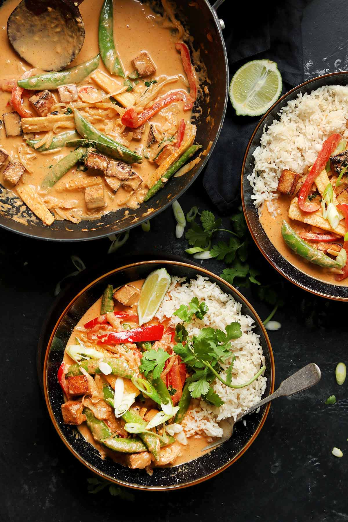 Marinated crispy tofu with peppers in a Thai red curry sauce, with rice and coriander garnish in bowls.
