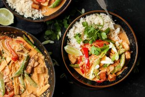 Marinated crispy tofu with peppers in a Thai red curry sauce, with rice and coriander garnish.