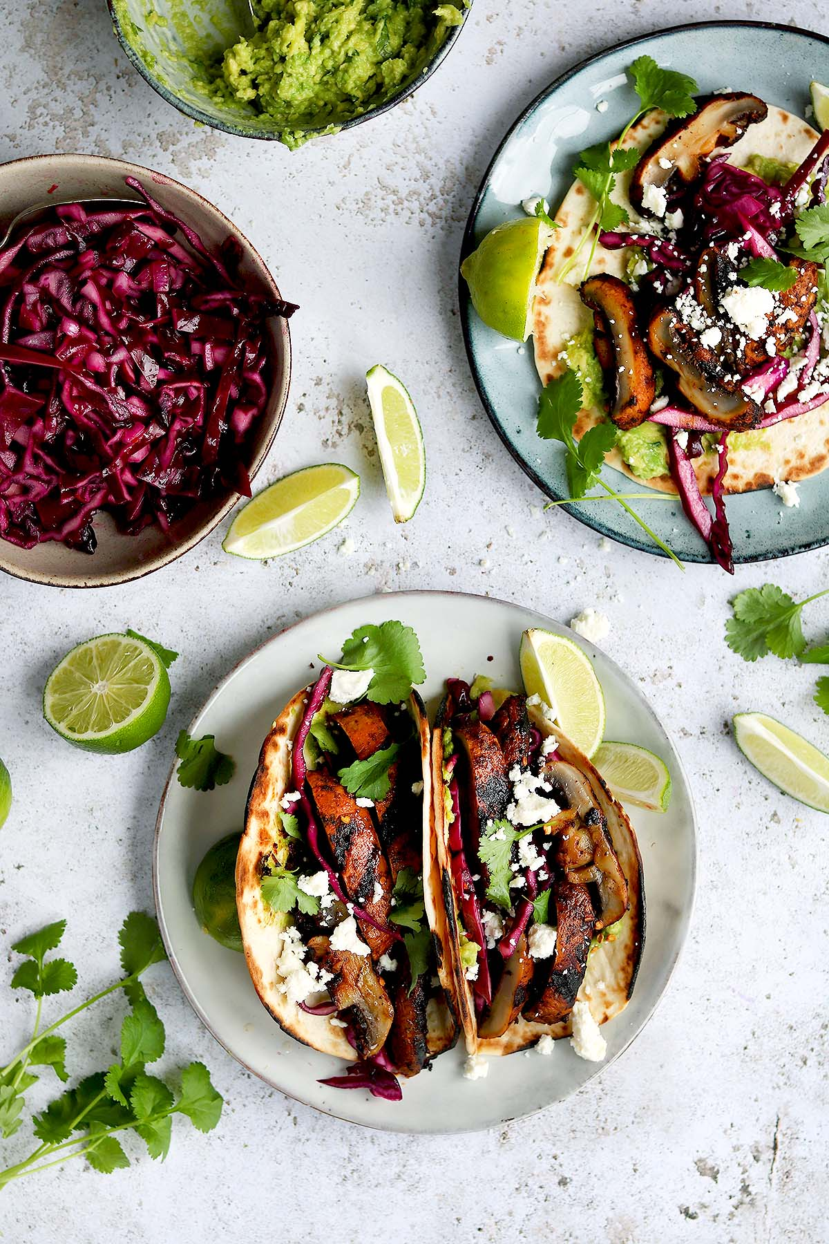 Mushrooms in a Taco with Red Cabbage Slaw and smashed Avocado, with Lime wedges and Coriander garnish.