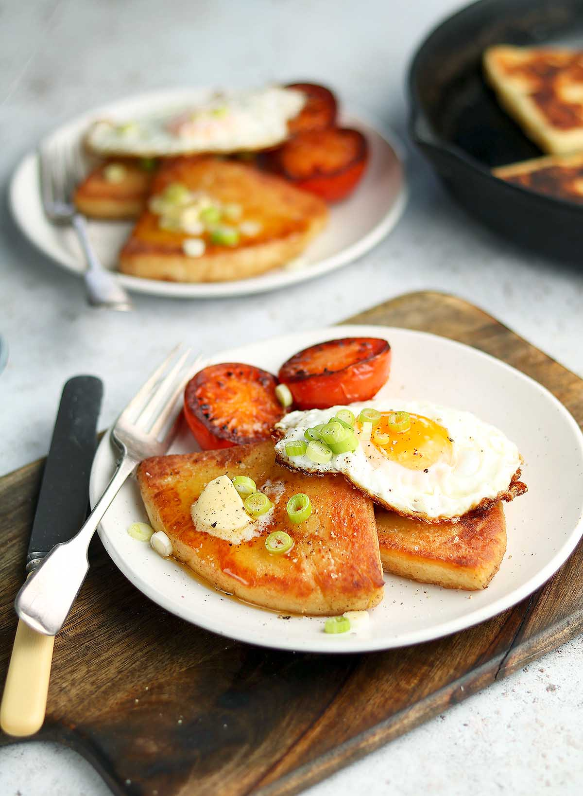 Fried Potato served with tomatoes and a fried egg with sprint onion garnish.