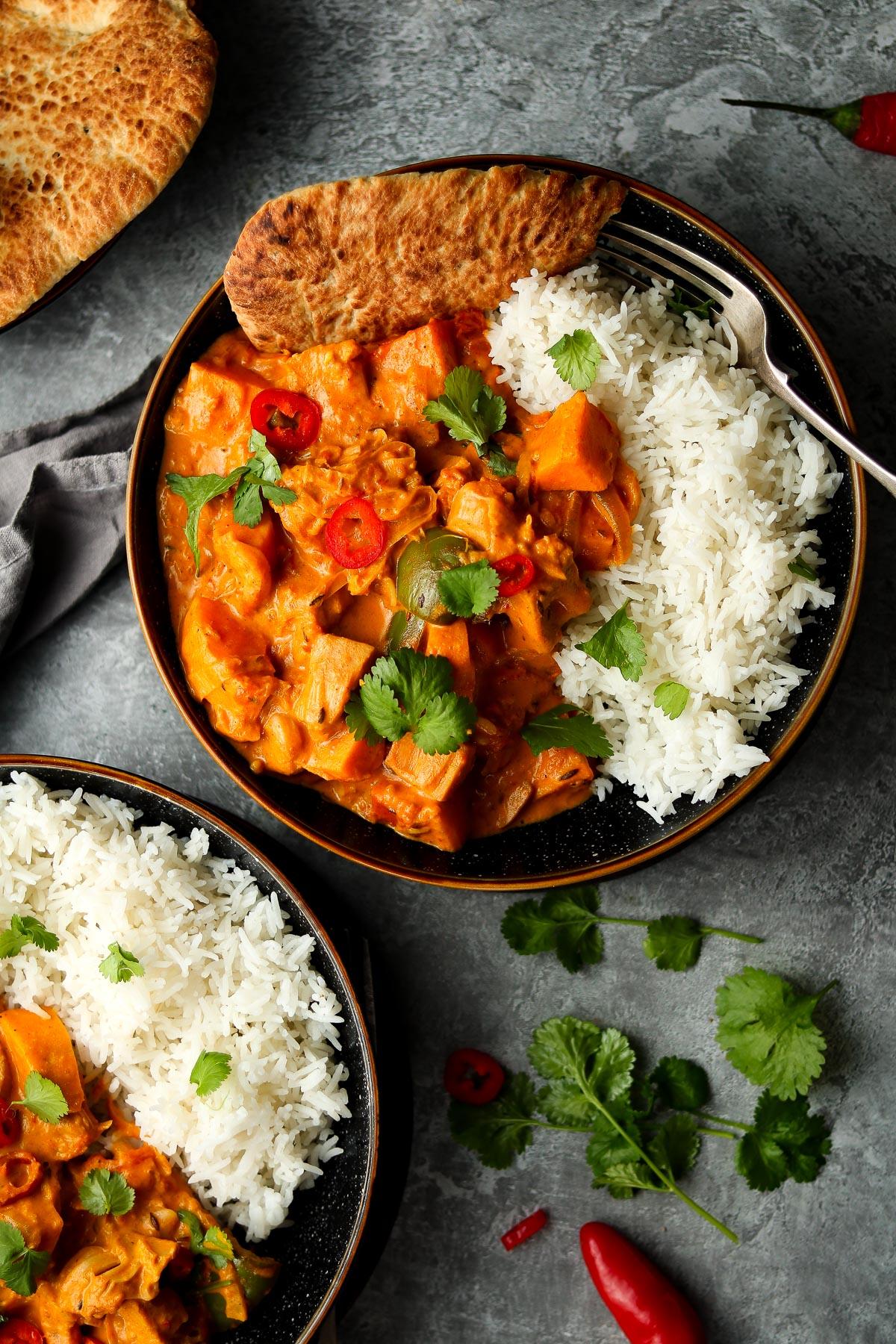 A jackfruit curry with sweet potatoes with rice and naan, with a coriander and chili garnish.